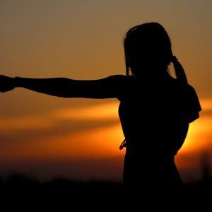 golden sunset with the silhouette of a woman in the foreground punching her arm out to the left