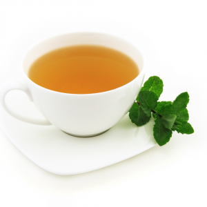 a white cup and saucer with an orange coloured tea and mint leaves on the side