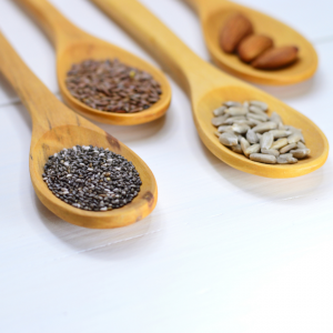 4 wooden tablesoons on a white table top with chia seeds, flax seeds, sunflower seeds, and almonds