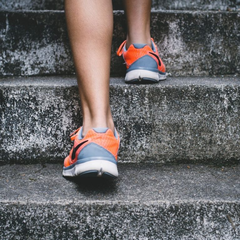 Legs from the calves down climbing up concrete stairs in grey and orange shoes