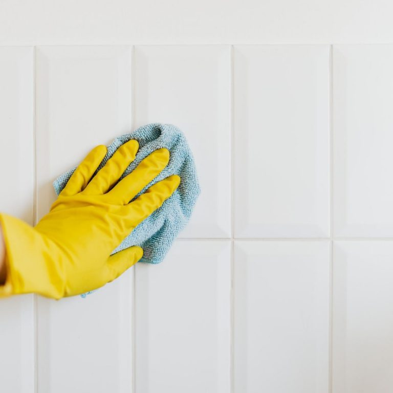 yellow gloved hand with a blue cleaning cloth on white tile