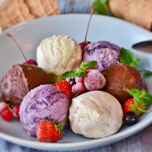 6 scoops of ice cream and sorbet (chocolate, vanilla, berry) arranged alternatingly in a circle on a white plate with frozen strawberries in the centre
